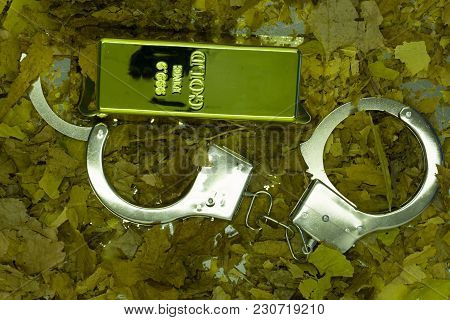 The Gold Bar Put In The Metal Name Card Box And Chrome Metal Handcuffed Represent The Crime And Busi
