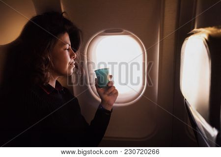Young Caucasian  Woman Drinking Coffee  Inside Airplane Sitting On Passenger Seat Near Window, Relax