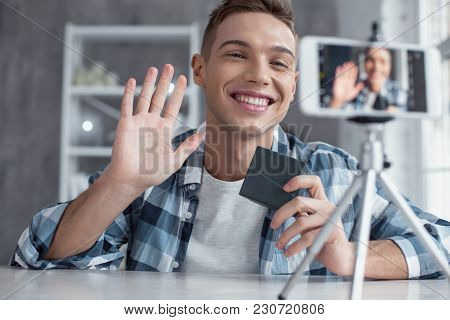 Hello Guys. Good-looking Happy Popular Well-built Blogger Holding A Box And Waving While Making A Vi
