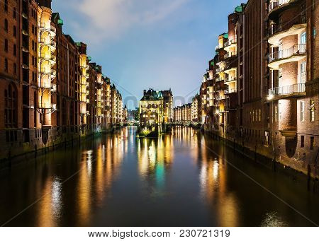 Long Time Exposure Shot Of Canal Amidst Illuminated Buildings In Old Warehouse District Speicherstad