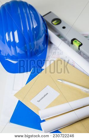 Termination Notice In A Brown Envelope Lying On An Engineer Or Architects Desk Amongst Blueprints An