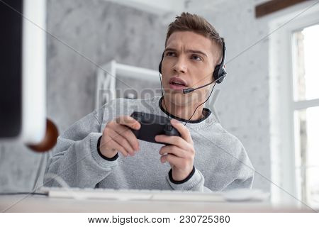 Favourite Computer Game. Attractive Determined Fair-haired Teenager Wearing Headphones While Playing