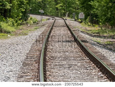 Train Track Curves To The Left On Its Way Out Of A Small Town