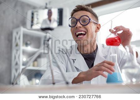 In High Spirits. Attractive Exuberant Fair-haired Teenager Wearing A Uniform And Glasses And Holding