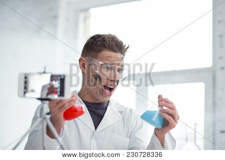 Irritated. Handsome Angry Fair-haired Young Blogger Wearing Uniform And Holding Test Tubes And Makin