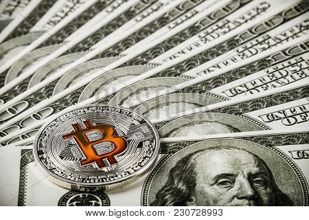 Bitcoin Coin On Background Of Banknotes Of Dollars. Bitcoin Is The Most Popular Cryptocurrency In Th