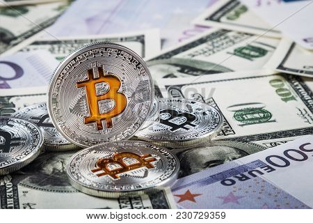 Bitcoin Coins On Background Of Banknotes Of Dollars And Euros. Bitcoin Is The Most Popular Cryptocur
