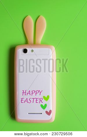 White Phone With Light Orange Bunny Ears And Three Little Colorful Hearts On Bright Green Background