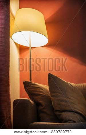 Floor Lamp Stands In The Room Or Hotel Room Against The Backdrop Of Furniture. The Interior Of The R