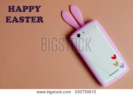 White Phone With Pink Bunny Ears And Three Little Colorful Hearts On Orange Background With Copy Spa