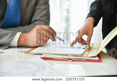 Businessman In Grey Suit Are Discussing With Businesswoman At Meeting. Business People Hands Are Poi