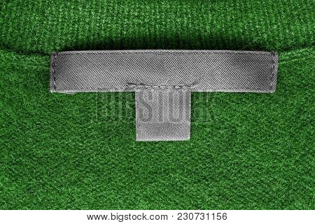 Blank Textile Clothes Label On Green Wool Knitted Background Closeup