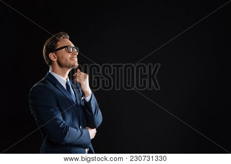 Stand And Check. Pleasant Concentrated Stylish Man Standing In The Empty Room Holding Hand Near His