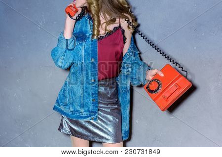Partial View Of Woman Talking On Retro Telephone Against Concrete Wall