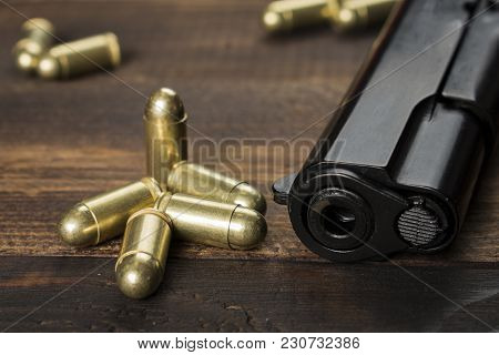 Cartridges With A Gun On A Wooden Table