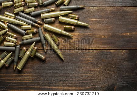 Cartridges Of Different Calibers On A Wooden Table With A Place For Inscription
