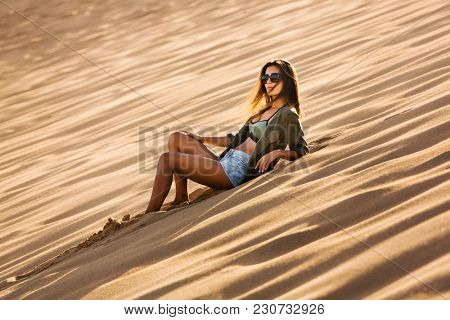 Beautiful young woman lying on a sand dune