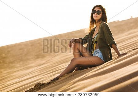 Beautiful young woman sitting on a sand dune