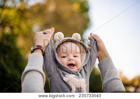 Little Baby Boy Dressed In A Warm Clothes Lying On A Blanket In The Autumn Park
