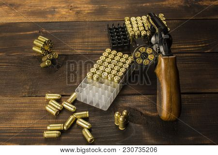 Revolver With Cartridges On The Wooden Table