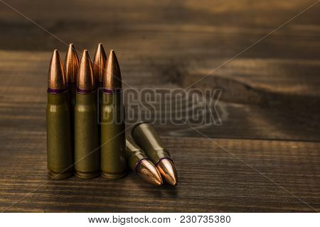 Cartridges To Ak47 On A Wooden Table