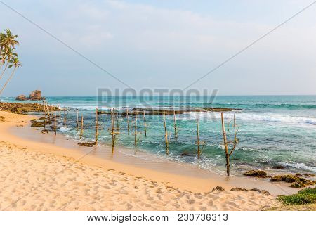Beautiful Seascape, Boulders, Palms And Place Of The Traditional Fishermen On Stilts, Sri Lanka.