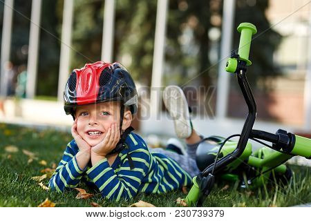 Portrait Of A Positive Little Boy In Stripped T-shirt And Protective Helmet On A Bicycle Outdoor, Se