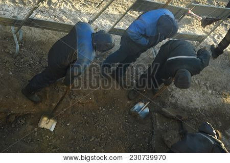 Working Men In The Form Of Standing Around A Sand Pit
