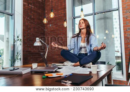 Female Student Sitting In Lotus Pose On Table In Her Room Meditating Relaxing After Studying And Pre