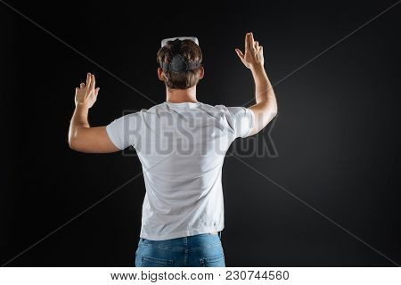 New World. Impressed Curious Stylish Man Standing In The Empty Room Lifting Hands And Using Vr Glass