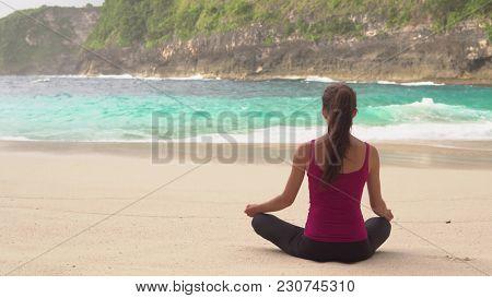 Woman Meditates In Yoga Asana Padmasana - Lotus Pose On Ocean Shore