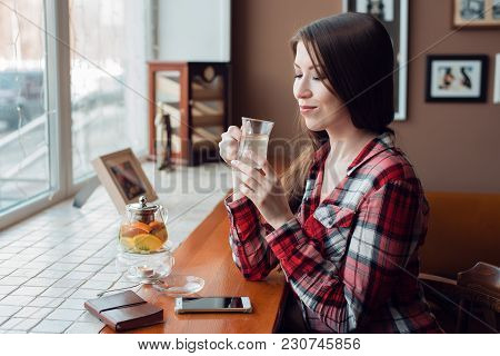 A Female Student In A Shirt Is Smiling Happily, In The Daytime At Cafe By The Window, She Dreams And