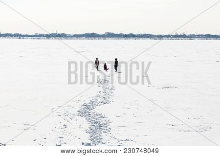 The Family Walks On The Ice Of The River. Winter Day.
