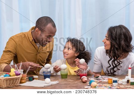African American Parents And Daughter Painting Easter Eggs And Holding Them Above Glasses With Paint
