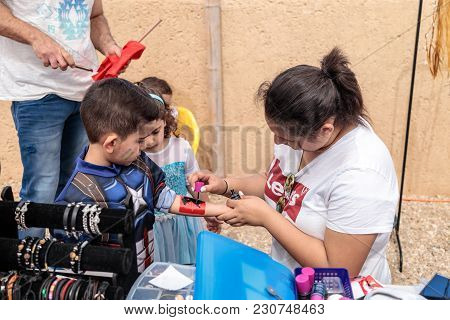 The Participant Of The Purim Festival Puts A Drawing On The Boy's Hand In Caesarea, Israel