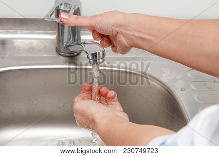 Physician Is Washing His Hands Under Tap Water. Preparation For Medical Procedures
