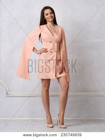 Attractive Brunette Female Model Wearing Mini Pink Dress With Golden Buttons, Split, Long Hanging Sl