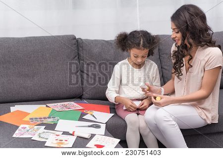 African American Mother And Daughter Gluing Paper For Greeting Card On Mothers Day