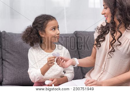 African American Mother Giving Daughter Piece Of Paper For Greeting Card On Mothers Day