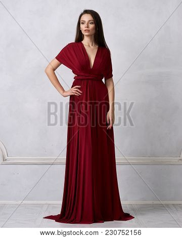 Beautiful Long Haired Young Woman Dressed In Stylish Cherry Red Bandeau Maxi Dress Posing Against Wh