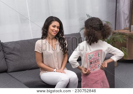 Back View Of African American Daughter Presenting Greeting Card To Mother On Mothers Day