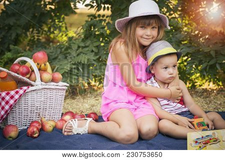 Happy Cute Little Girl And A Boy Are Sitting On A Blanket In The Park And Playing In A Beautiful Sun