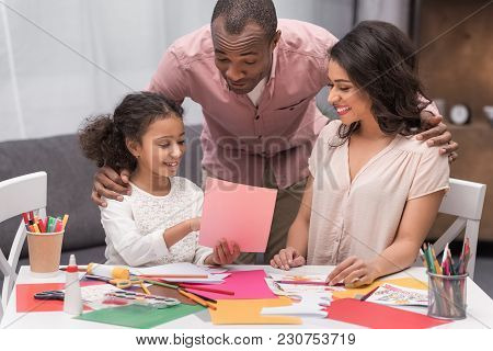 African American Daughter Showing Parents Sketch Of Greeting Card On Mothers Day