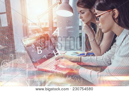 Two Women Working On New Website Design Choosing Pictures Using The Laptop Surfing The Internet.
