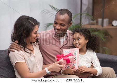 African American Daughter And Husband Presenting Gifts To Wife On Mothers Day