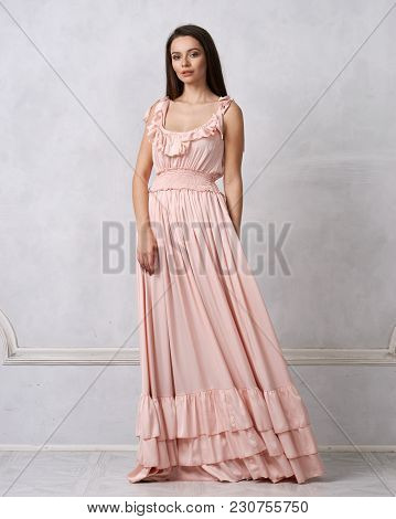 Full body portrait of gorgeous young brunette woman dressed in exquisite nude ball gown with lace top. Attractive female model in elegant strapless dress posing against white wall on background. poster
