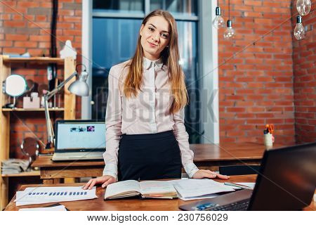 Female Manager Standing At Her Workplace Planning Her Working Day Reading Notes Made In Notebook.
