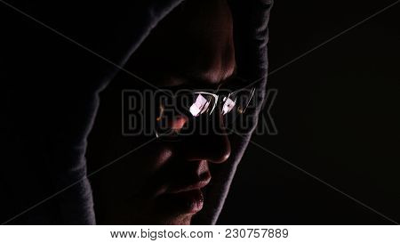 Hacker In Glasses And A Hood Works At A Computer In The Dark, A Reflection In Glasses Close-up, 4k