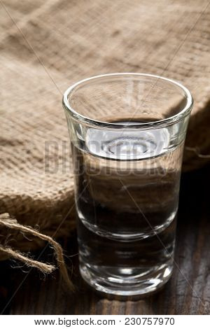 German Hard Liquor Korn Schnapps In Shot Glass With Burlap Sack On Rustic Wooden Table
