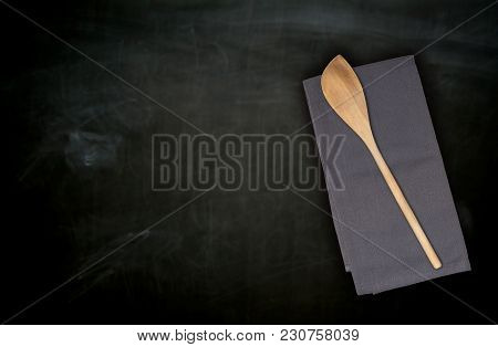 Wooden Spoon And Kitchen Towel On Blackboard.